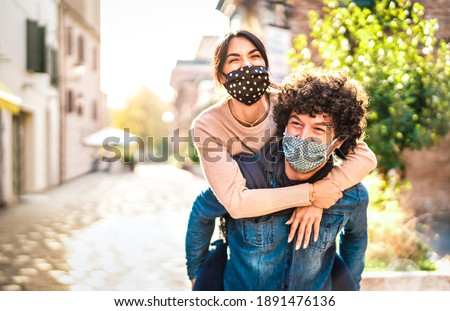 Happy couple of lovers enjoying time outdoor at Valentines day - Handsome guy with nice girl on piggy back moment - New normal love concept with boyfriend and girlfriend together on warm vivid filter Royalty-Free Stock Photo #1891476136
