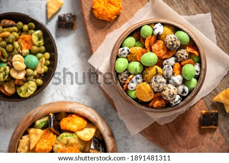 Various Japanese snacks in a wooden bowl close-up. Rice crackers with wasabi and nori, peanuts with sesame seeds, and other snacks. Mix traditional Japanese snack food. Royalty-Free Stock Photo #1891481311