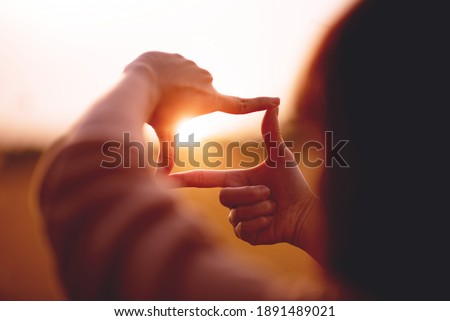 New year planning and vision concept, Close up of woman hands making frame gesture with sunset, Female capturing the sunrise. copy space. Royalty-Free Stock Photo #1891489021