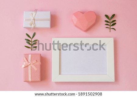 Flat lay with photo frame with place for message. Greeting card with Happy Mothers Day, Womens Day, Valentines Day or Birthday. Gifts and heart on a pink background