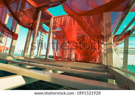 Abstract photographic picture with red sails. Red sails flutter in the wind on white frames on the seashore.