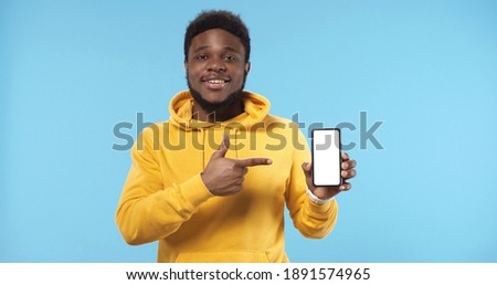 Portrait of happy African american man showing blank screen mobile phone standing isolated over blue background.
