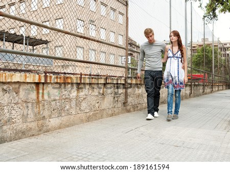 Attractive teenagers boyfriend and girlfriend walking together passed a college university building and sports ground holding each other during a weekend break in an urban city. Youth lifestyle. #189161594