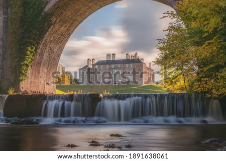 Dalkeith Country Park with waterfall and arch framing manor house on a sunny autumn afternoon makes for an ideal day trip from Edinburgh in Scotland. Royalty-Free Stock Photo #1891638061