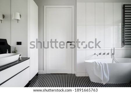 Luxury black and white bathroom with freestanding bathtub, stylish mosaic tile floor and white doors with black handle Royalty-Free Stock Photo #1891665763