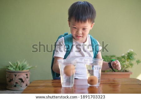 Happy smiling excited little Asian school kid studying science, doing fun and easy Floating Egg Science Experiment to learn about the density of salt water effect to floating and sinking of the eggs Royalty-Free Stock Photo #1891703323