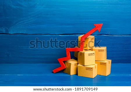 Cardboard boxes and red arrow up. Transformation of the economy and trade into online marketplaces, the growth of e-commerce and online shopping. Growing business activity. Rise in price of goods. Royalty-Free Stock Photo #1891709149