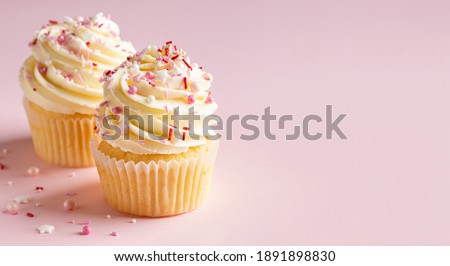 Vanilla cupcakes with cream cheese frosting and pink sprinkles on pink background. Saint Valentine's day or birthday dessert. Beautiful festive food for wedding or baby shower girl. Copy space. Royalty-Free Stock Photo #1891898830