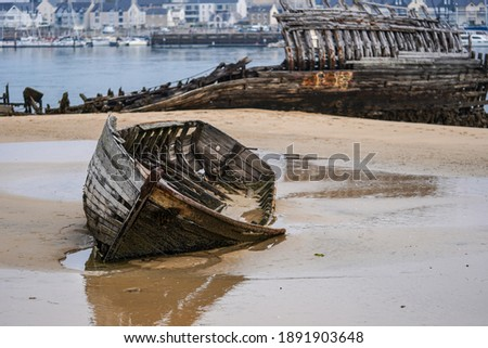Stranded fishing boats on the beach. Historical wreck in France. Royalty-Free Stock Photo #1891903648