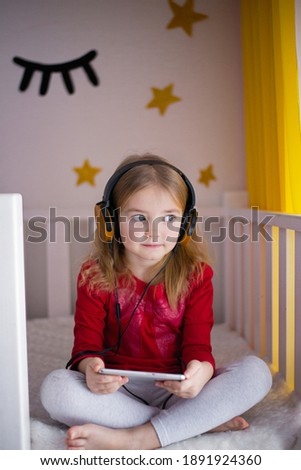 A little girl listens to a children's audiobook on her mobile phone with headphones in bed. Education, child development. E-book with fairy tales, cartoons in the children's room. she watches cartoons