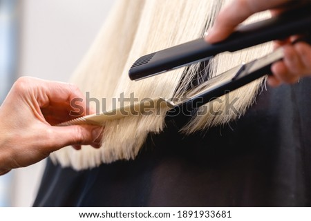 Hairdresser using a flat iron hair straightener to straighten woman's blonde hair Royalty-Free Stock Photo #1891933681