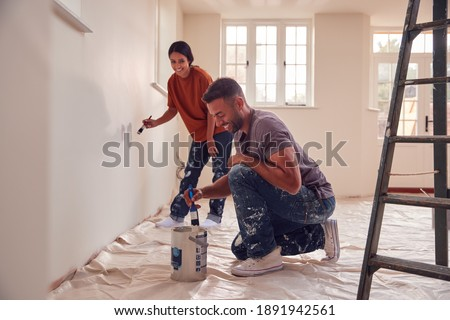 Couple Painting Test Squares On Wall As They Decorate Room In New Home Together Royalty-Free Stock Photo #1891942561
