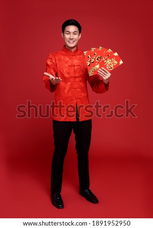 """Happy Chinese new year. Asian man holding angpao or red packet This word means """"happiness"""".monetary gift isolated on red background. Royalty-Free Stock Photo #1891952950"""