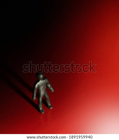 Psychology or religion concept - highlighted clay character standing and looking on spotlight with drop long shadow. Thematical conceptual photo