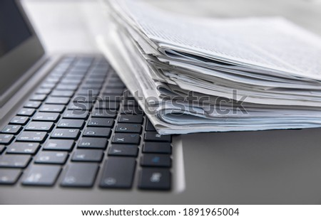 Newspapers and laptop. Pile of daily papers with news on the computer. Royalty-Free Stock Photo #1891965004