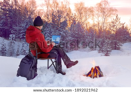 Rear view of male traveler blogger work remote on laptop while enjoying winter nature landscape view outdoors.