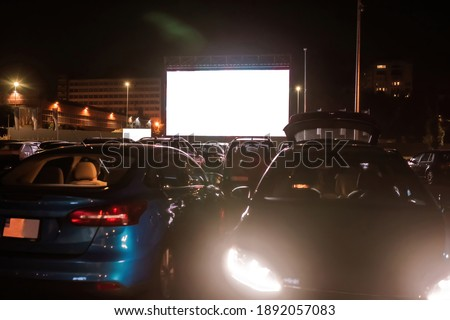 The best place to go. Many cars parked in front of a big white screen to watch movies or films sitting inside the car at drive in cinema in the evening. Entertainment, hobby concept Royalty-Free Stock Photo #1892057083