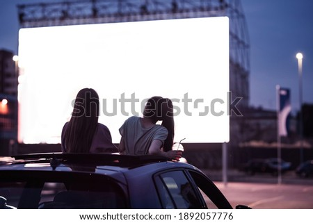 Rear view of two female friends sitting in the car while watching a movie in an open air cinema with a big white screen. Entertainment concept. Focus on people. Horizontal shot Royalty-Free Stock Photo #1892057776