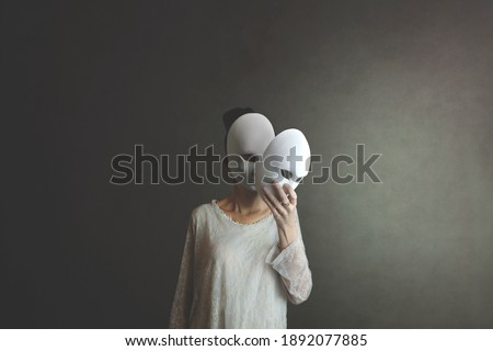 woman takes off the mask from her face but underneath her she has another mask, concept of hiding one's soul and oneself Royalty-Free Stock Photo #1892077885