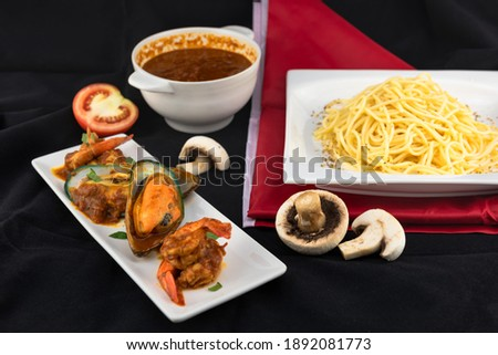 The picture of a large New Zealand mussel with ingredients such as shrimp, champignon mushroom, tomato, spaghetti, tomato sauce,  all used for cooking pasta dishes.