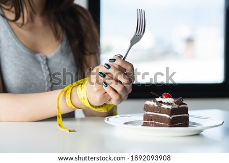 diet for good health concept. Woman tied her hand and restraint do not to eat sweet food. Royalty-Free Stock Photo #1892093908