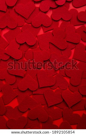 A vertical shot of red heart shape cutouts on the table - great for romantic backgrounds
