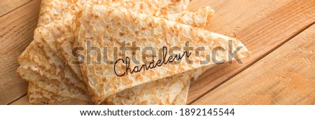 Close up on a stack of folded crepes (french pancakes) on panoramic wooden background, word Chandeleur Royalty-Free Stock Photo #1892145544