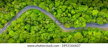 Winding road, top view of beautiful aerial view of asphalt road, highway through forest and fields in rainy season. For traveling and driving in nature. Banner panorama background