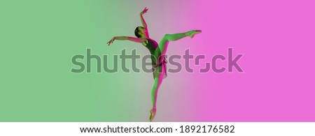 Flyer, copyspace. Young and graceful ballet dancer isolated on gradient pink-green studio background in neon. Art, motion, action, flexibility, inspiration concept. Flexible ballerina, weightless Royalty-Free Stock Photo #1892176582