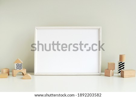 Blank horizontal frame mockup, nursery framed wall art, baby room art, empty frame for print, photo, wooden shelf, wooden toys.  Royalty-Free Stock Photo #1892203582