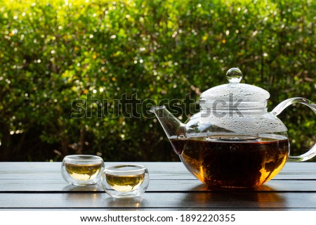 picture of people pouring hot water into clear glass kettle to make tea in afternoon in garden