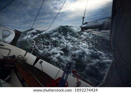 Heeled yacht sailing in the sea during the storm, a view from the cockpit. Dark waves, water splashes. Long exposure, motion. Rough weather, cyclone, danger, epic seascape. Regatta, racing, sport Royalty-Free Stock Photo #1892274424