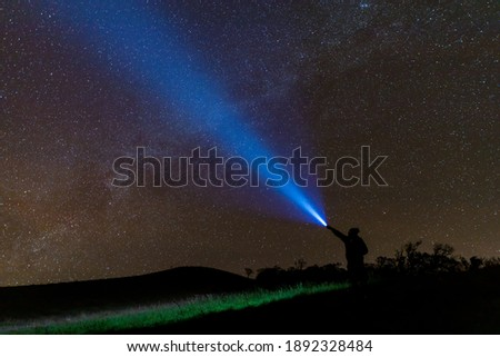 Climber or backpacker. Light holds up over his head. Standing on mountain peak. man with flashlight point to the starry sky at midnight. tourist with flashlight Royalty-Free Stock Photo #1892328484