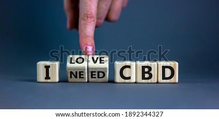 I love CBD, cannabidiol symbol. Hand turns cubes and changes words 'I need CBD' to 'I love CBD'. Beautiful grey background, copy space. Medical and i love CBD cannabidiol concept. #1892344327