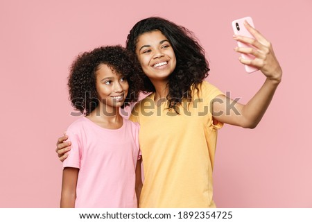 Smiling african american young woman and little kid girl sisters in casual t-shirts hugging doing selfie shot on mobile phone isolated on pastel pink background studio portrait. Family day concept