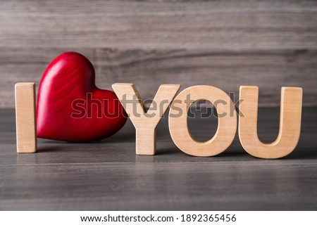 Phrase I Love You made of decorative heart and letters on wooden table, closeup