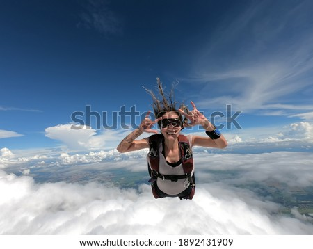Young woman parachutist smiling in free fall. Perfect concept of happiness and freedom. Royalty-Free Stock Photo #1892431909