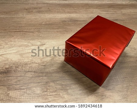 paper big square red box on wooden table. Gift wrapping with surprise  is not visible what gift inside. simple and stylish white present. Space for text or postcard. No one and simple picture