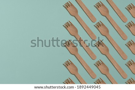 Group of wooden forks on green background with copy space