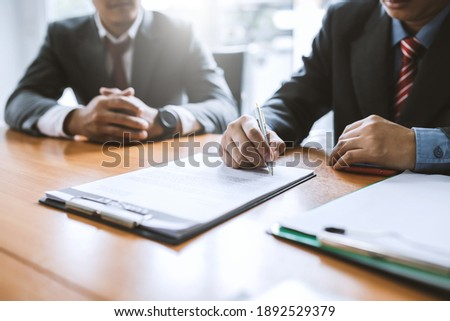 Signing a business contract. Group of business people at the meeting and sign a together business investment agreement.