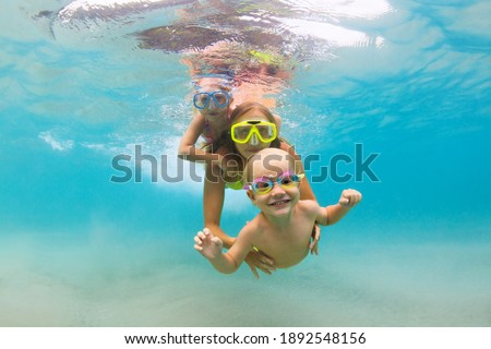 Young mother, baby boy, girl jump, dive underwater with fun in tropical lagoon pool. Travel lifestyle, water sport, snorkeling adventure. Family swimming lesson on summer sea beach vacation with kids
