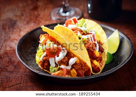 Delicious spicy tacos with meat, salsa and vegetables drizzled with sour cream and served with lemon wedges for a savory snack or lunch #189255434