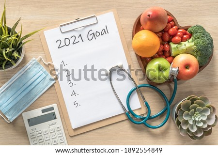 2021 New Year Goals in new normal lifestyle, work-life balance with face mask safety awareness from covid-19, healthy food, good heart health, blank resolution list on white paper medical clipboard Royalty-Free Stock Photo #1892554849