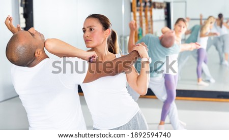 Young Latina paired up with male partner in self defense training, practicing elbow hit in close combat Royalty-Free Stock Photo #1892594740