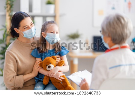 Doctor, child and mother wearing facemasks during coronavirus and flu outbreak. Virus protection. COVID-2019. Taking on masks. Royalty-Free Stock Photo #1892640733