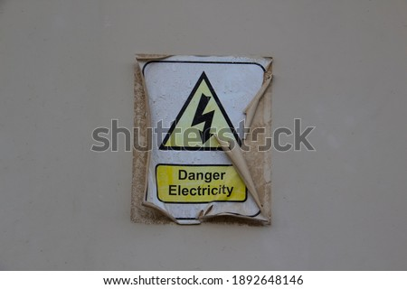 Electric danger symbol with a words DANGER ELECTRICITY. Sticker is old and peeled off and burnt-out  Royalty-Free Stock Photo #1892648146