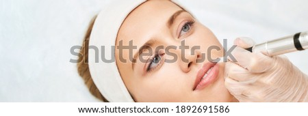 Permanent makeup. Beauty spa procedure. young woman. Face tattoo. Lip micropigmentation. Professional face microblading. Female cosmetology device. Copyspace. Mouth treatment. Dermatology Royalty-Free Stock Photo #1892691586