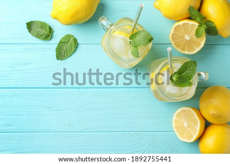 Natural lemonade with mint on light blue wooden table, flat lay and space for text. Summer refreshing drink Royalty-Free Stock Photo #1892755441