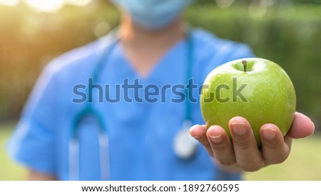 World health day, an apple a day keeps the doctor away concept for health benefit by eating high nutritious clean food and healthy nutritional diet with doctor handling green apple giving to patient Royalty-Free Stock Photo #1892760595