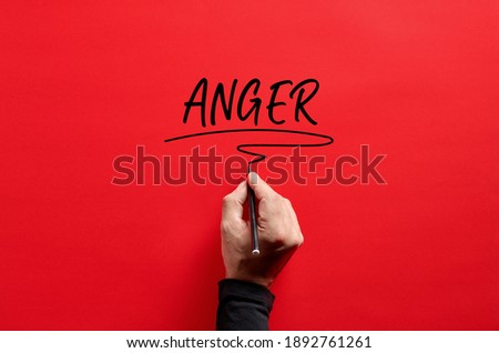 Male hand writing the word anger on red background. Anger management concept. Royalty-Free Stock Photo #1892761261